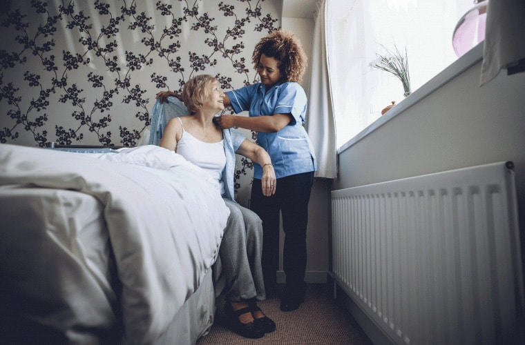 Carer helping a lady get dressed