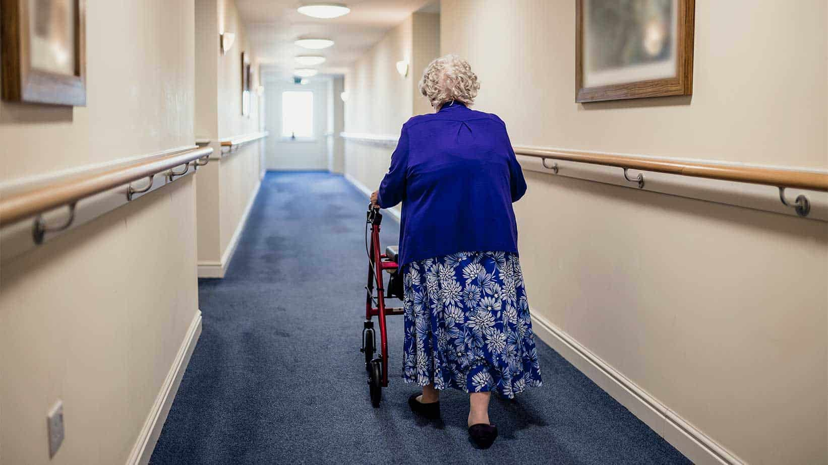 Old lady walking down a corridor on a zimmer frame